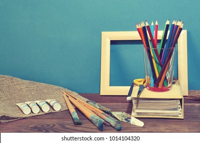 Designer desk with colored crayons, brush, pencils and paints. Top view . Flat lay image.Working desk table concept. - Shutterstock ID 1014104320