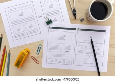 Designer desk with website wireframe sketches. Flat lay