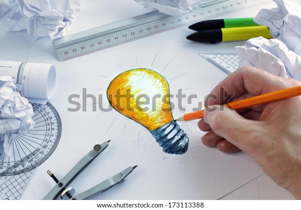 Designer, der eine Glühbirne zeichnet, Konzept für Brainstorming und Inspiration