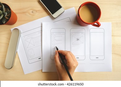 Designer drawing mobile application wireframe on wooden desk. Top view