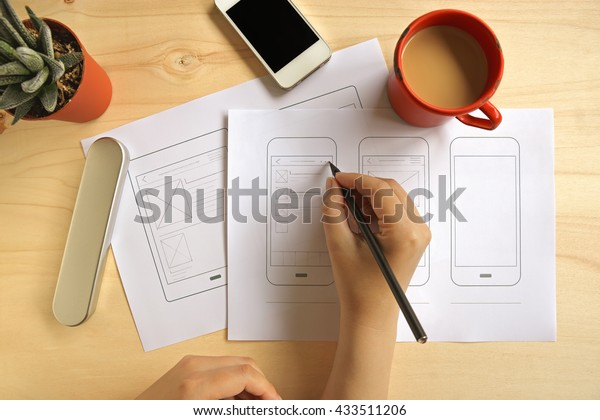 Designer drawing mobile application wireframe on wooden desk. Flat lay