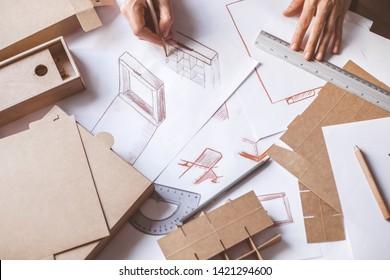 Designer draws a mockup for crafting cardboard box. Development of packaging design sketch.