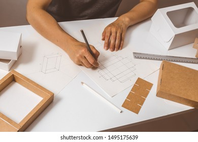 Designer draws a mockup for crafting eco cardboard box. Development a sketch of paper packaging.