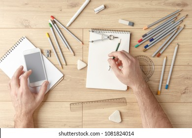 The designer draws a sketch in a notebook on a wooden table. Stationery. View from above.
