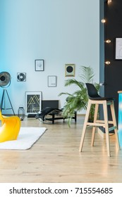 Designer eclectic loft with barstool, lamp and posters on white wall and wooden floor