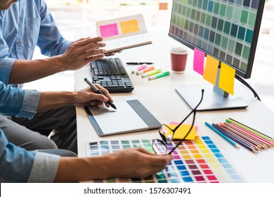 designer graphic creative creativity working together coloring using graphics tablet and a stylus at desk with colleague