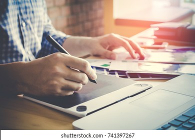 Designer graphic creative  working on Mouse pen,laptop in  office