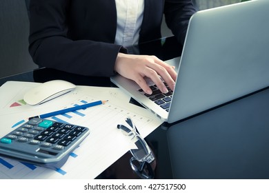 designer hand working with digital tablet and laptop and notebook stack and eye glass on desk in office