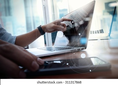 designer hand working and smart phone and laptop on wooden desk in office with london city background with social network diagram