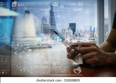 designer hand working and smart phone and laptop on wooden desk in office with london city background