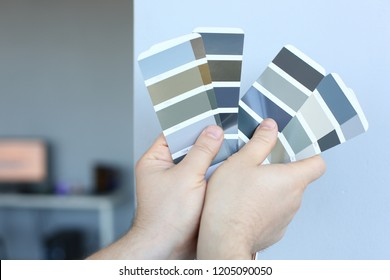 The designer holds pantone fan of color guide in hand. Selection of colors for the color of the walls apartment distribution during promotion concept