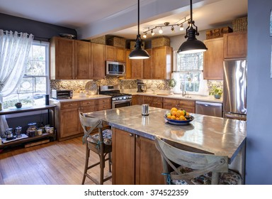 Designer kitchen remodel in eclectic style with stainless steel and stone