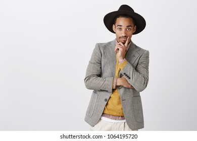 Designer looks at model in his clothes. Portrait of classy handsome young man in stylish formal outfit and hat, holding hand on chin, staring curiously at camera, being interested in discussion