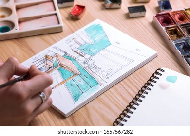 designer makes a sketch of the kitchen interier. background - sketch, watercolor paints, brushes, palette, glass with water
