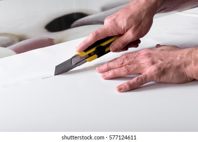 Designer male hands close-up shot making cuts of white wide sheet of paper using professional utility knife cutter