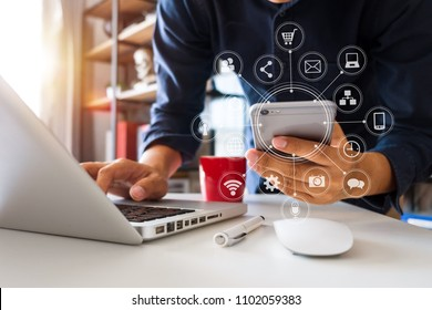 designer man using smart phone for mobile payments online shopping,omni channel,sitting on table,virtual icons graphics interface screen in morning light