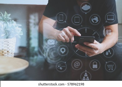 designer man using smart phone for mobile payments online shopping,omni channel,sitting on sofa in living room,vase rattan with plant and wooden tray on table,virtual icons graphics interface screen