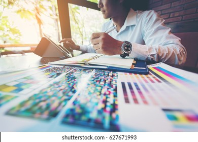 designer man working graphic with color chart and write short note for choose a color in office
