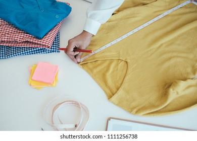 Designer measuring the long sleeve shirt.