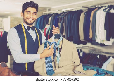 Designer is picking up a tie for light jacket in the shop.