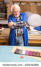 The designer reflects on the design of the furniture, chooses the color of the finishing material behind the cutting table in the workshop of a small furniture factory