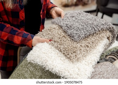 Designer shows examples of carpet rugs in textile store.