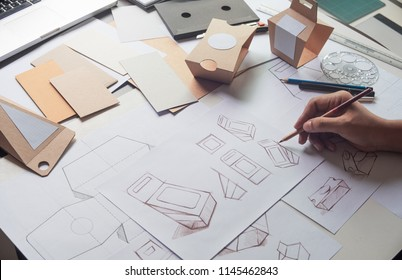 Designer sketching drawing design Brown craft cardboard paper product eco packaging mockup box development template package branding Label . designer studio concept .