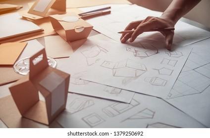 Designer sketching drawing design Brown craft cardboard paper product eco packaging mockup box development template package branding Label . designer studio concept .