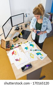 Designer, standing behind her desk in a design studio, reviewing a large variety of conceptual design drawings and sketches