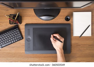 Designer using graphic tablet in the office. Top view workplace with tablet, keyboard and computer.
