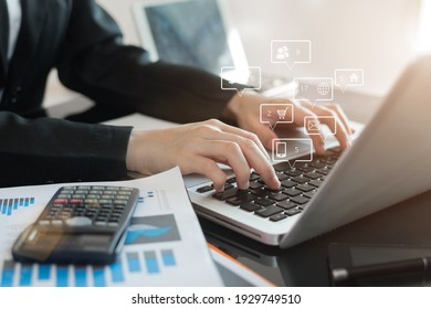Designer using laptop and document on desk in office with virtual interface graphic icons network diagram.