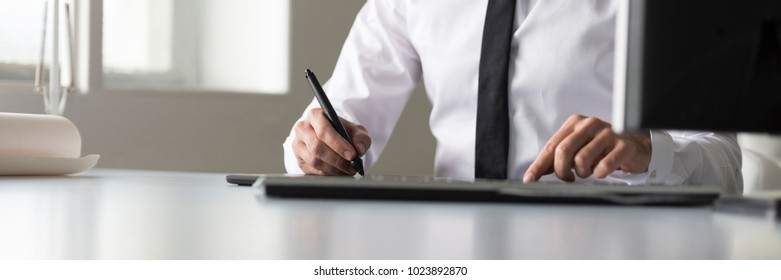 Designer using a tablet and stylus pen in wide panorama low angle view across the office table.