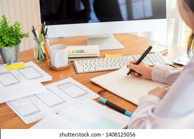 Designer woman drawing a website outline and website ux app development on mobile phone.