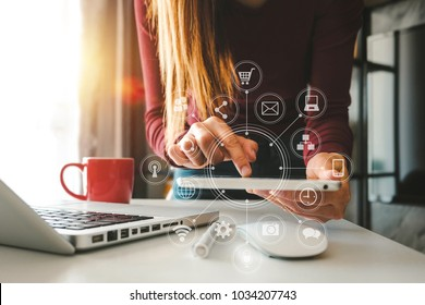 designer woman using smart phone for mobile payments online shopping,omni channel,sitting on table,virtual icons graphics interface screen in morning light