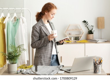 Designer At Work. Young tailor standing at her home office during quarantine, holding notebook anf coffee mug, copy space
