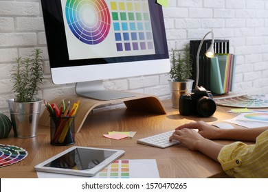 Designer working with computer at wooden table, closeup