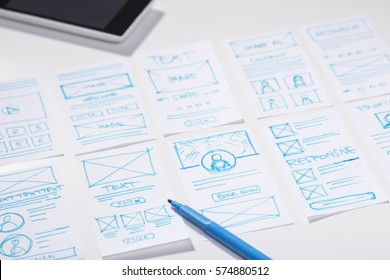 Designer working desk with wireframe sketches for mobile application, user interface design process