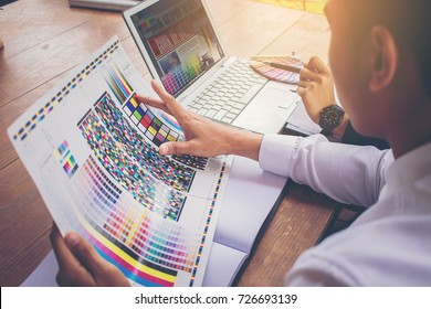 designer working graphic with color chart and write short note for choose a color in office