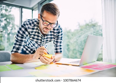 Designer working from home office taking notes