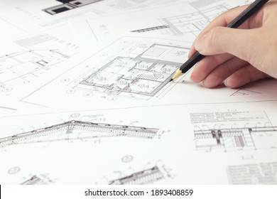 Designer are working on a new project blueprint Design at desk in office. Architects workplace - architectural project and hand with pencil. Architectural plans