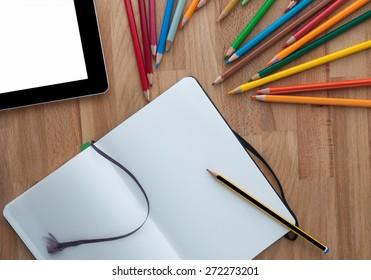 Designer workspace with tablet and Notebook  on wooden desk background