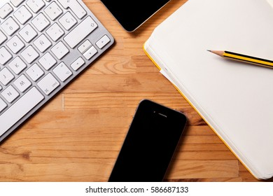 Designer workspace with tablet, Notebook and smart phone on wooden desk background