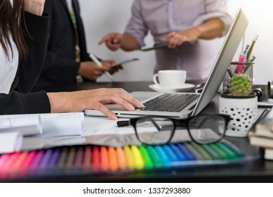 Designer Young asian using graphics tablet while working with computer at studio or office,Graphic design and color swatches and pens on a desk warm colours sun light.