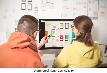 Designers are developing web applications for mobile phones sitting at the monitor screen in the office. User interface for smartphones.