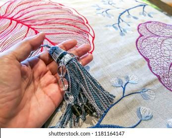 Designer's hand selective of vintage tassels & fabric sample for curtains decoration / Home interior remodel concept