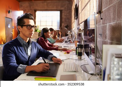 Designers Working At Desks In Modern Office