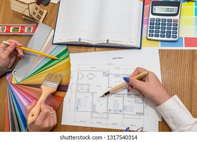 Designer's workspace with house plan and colour palette, top view