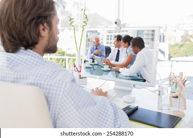 Desinger working on his computer against group of business people brainstorming together