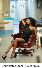 Desirable black woman in short dress and heels sitting in vintage armchair posing seductively