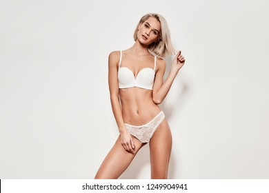 Desirable woman. Seductive young woman in lingerie looking at camera and smiling while standing against grey background
